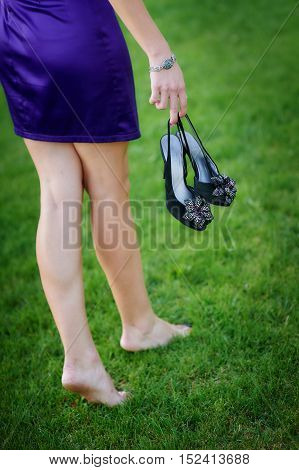 beautiful woman with shoes in hands on summer meadow.