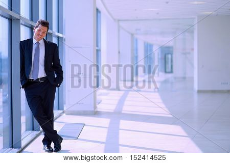 Successful businessman standing in hallway his company near window