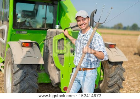 Portrait of a smiling farmer holding a pitchfork while working in his field