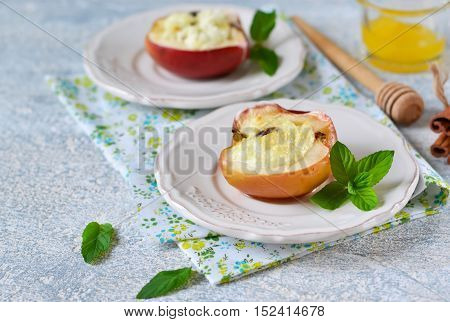 Apples baked with cheese raisins honey and cinnamon on a concrete background