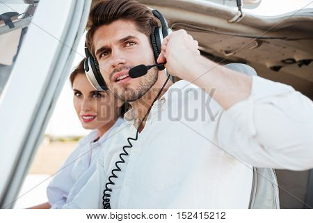 Close up portrait of a young pilot and beautiful stewardess sitting together inside airplane cabin waiting to take off
