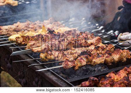 Marinated shashlik preparing on a barbecue grill over charcoal. Shashlik or Shish kebab popular in Eastern Europe. Shashlyk (skewered meat) was originally made of lamb. Roast Beef Kebabs On BBQ Grill.