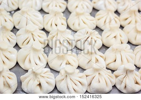 National Georgian cuisine Khinkali metal background Cook prepares khinkali kitchen Top view raw meat dough dish uncooked Street food booth selling Chinese specialty Steamed Dumplings Process cooking