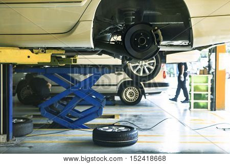 car wheel suspension and brake system maintenance in auto service before long journey