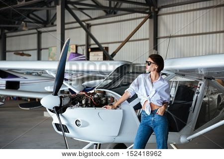 Beautiful young woman in sunglasses posing near plane while standing in angar