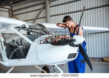 Concentrated young aircraftsman repairing small aircraft
