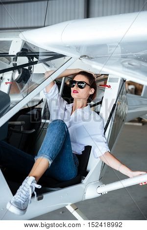 Beautiful young woman in sunglasses sitting inside small airplane