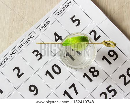Shot of tequila with a slice of lime on the calendar at friday. Weekend concept