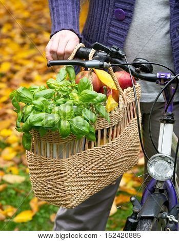 a shopping bag with apples and basil
