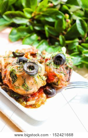 Chicken with tomato sauce, mushrooms and olives on plate