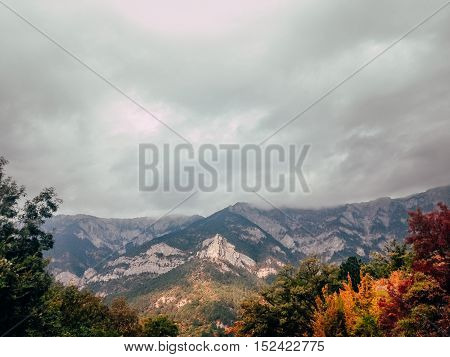 clouds over mountains of Crimea on slopes of autumn forest