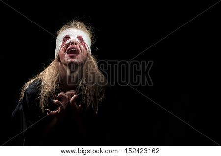 scared bloody girl screaming on black background with copyspace