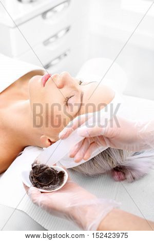 Chocolate mask. Beautician mask is applied to the woman's face