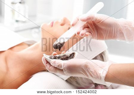 Sugar peeling, treatment in the beauty salon. Cleansing mask, a woman in the beauty salon.
