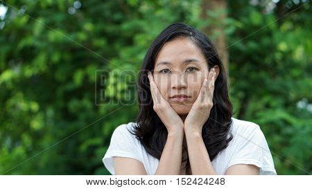 South East Asian Girl Looking At Camera Green Background