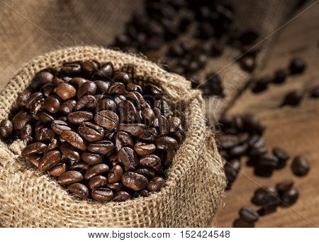Sack with coffee beans on a wooden background.