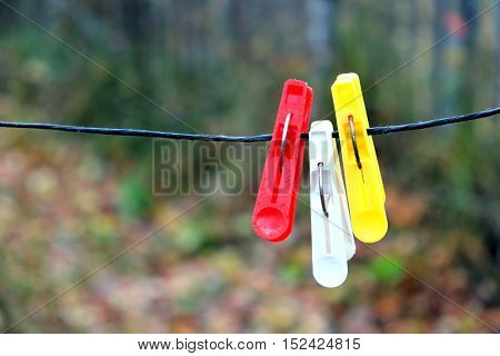 Three colored clothespins hanging on black rope on a blurred background in autumn day outdoors horizontal view closeup