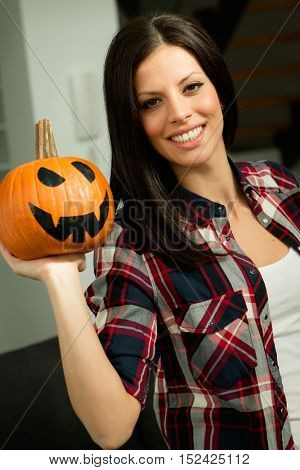 Attractive brunette woman at home with a halloween pumpkin