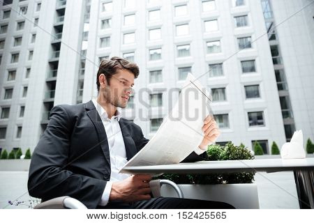 Concentrated young businessman reading newspaper in outdoor cafe