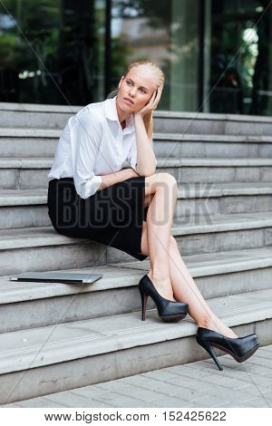 Full length of a blonde young woman sitting on the stairs woth laptop and looking away