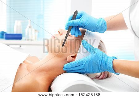 Plastic surgery, a woman in a plastic surgery clinic. White woman during surgery using a scalpel.