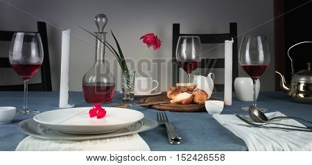 rose wine in glasses, bun, white candles on a blue tablecloth