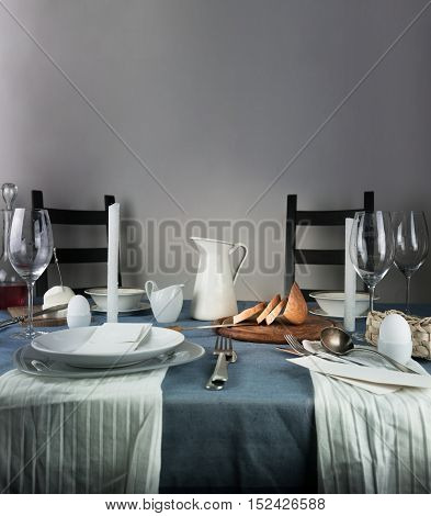 jug, glasses, bun, white candles on a blue tablecloth