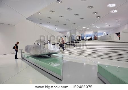 STUTTGART, GERMANY - APRIL 21, 2015. The white interior of the Porsche cars museum. The exposition of futuristic cars and visitors. Stuttgart, Germany.