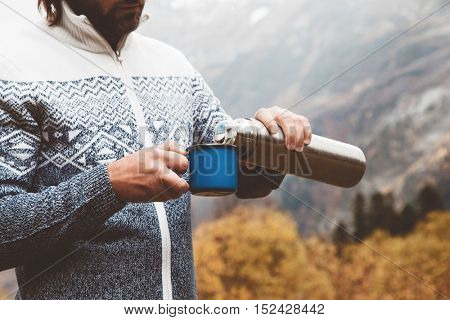 Hiker wearing sweater holding thermos and tin mug. Man drinking warm tea or coffee in the morning outdoor. Camping hiking concept. Autumn travel in mountains, cold weather. Noface photo.
