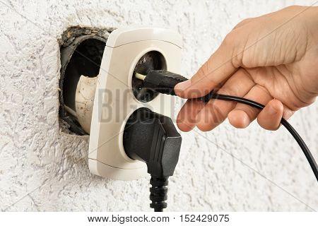 woman hand using broken dangerous electric socket
