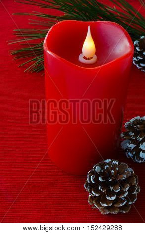 A large red flame less wax candle surrounded by a pine tree twig and pine cones on red fabric background.