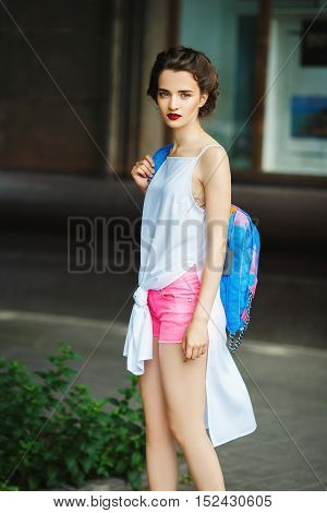 young woman with retro hair, with a blue backpack, beautiful makeup, white leather shoes, a white shirt and a pink shorts