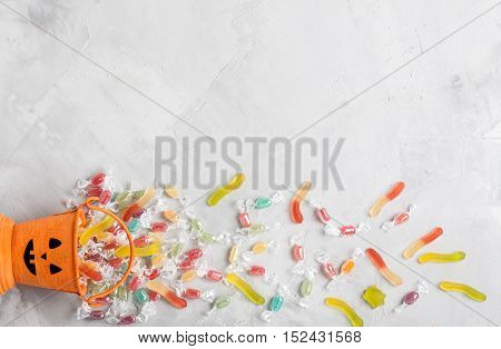 Halloween Bucket With Candies And Jujube On Gray Concrete Background
