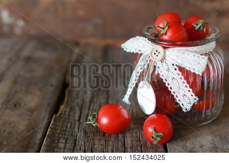 little sweet ripe red cherry tomatoes in a glass jar vintage