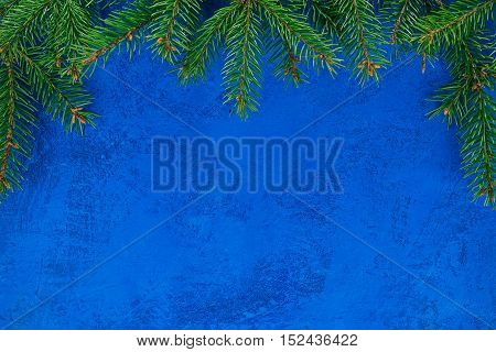 Top framework of evergreen twigs over painted blue surface