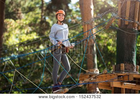 Pleasurable weekends. Happy optimistic energetic woman holding on to the ropes and smiling while standing on the rope ladder