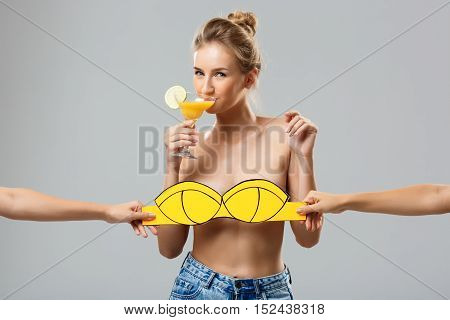 Hands covering beautiful blonde girl with cocktail in yellow swimwear over white background. Copy space.
