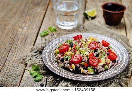 Red and white rice black beans corn avocado tomato salad.