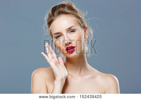 Young beautiful blonde nude girl with bright makeup looking at camera, posing over grey background. Copy space.