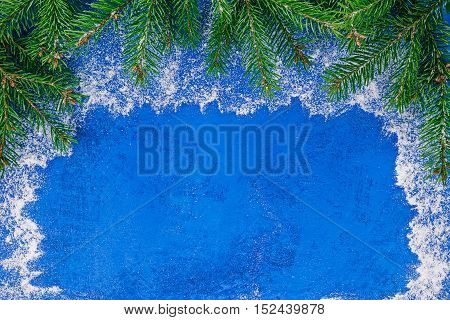 Top framework of evergreen twigs over painted blue surface covered with snow-like powder