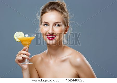 Young beautiful blonde naked girl smiling, holding cocktail over grey background. Copy space.