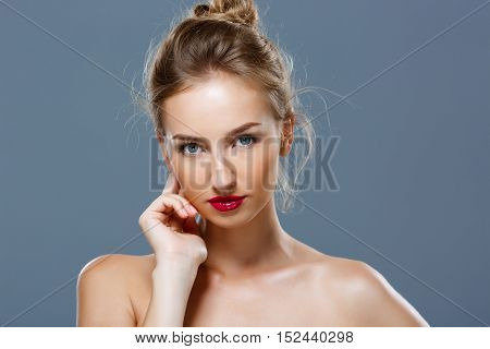 Young beautiful blonde girl with bright makeup posing over grey background. Copy space.