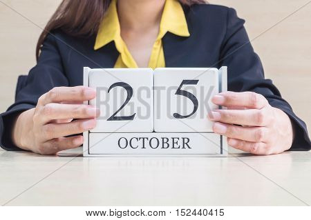 Closeup white wooden calendar with black 25 october word in blurred working woman hand on wood desk in office room selective focus at the calendar