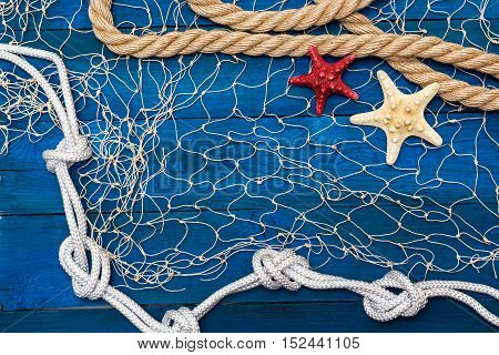 Marine network rope and starfish on a blue disk flat lay