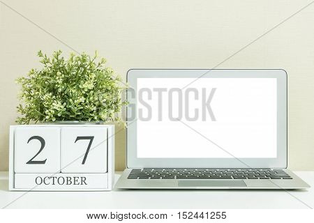 White wooden calendar with black 27 october word with white blank space at center of computer notebook on white wood desk and cream wallpaper textured background selective focus at the calendar