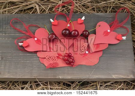 Red hearts on lace beautiful paper valentines day decor butterflies ripe sweet cherry and currant berry on brown wooden board and hay background