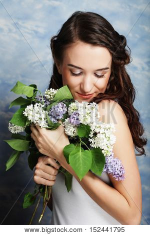 young beautiful woman with lilac flowers, studio shot
