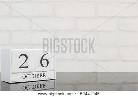 Closeup white wooden calendar with black 26 october word on black glass table and white brick wall textured background with copy space selective focus at the calendar