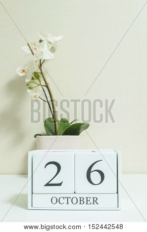 Closeup white wooden calendar with black 26 october word with white orchid flower on white wood desk and cream color wallpaper in room textured background selective focus at the calendar