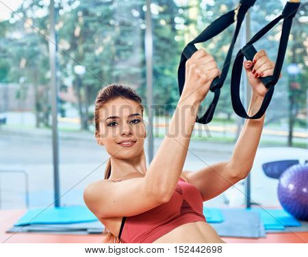 TRX. Beautiful sporty girl in the gym